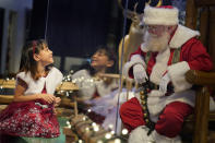 Gracelynn Blumenfeld, 8, visits with Santa through a transparent barrier at a Bass Pro Shop in Bridgeport, Conn., on Nov. 10, 2020. In this socially distant holiday season, Santa Claus is still coming to towns (and shopping malls) across America but with a few 2020 rules in effect. (AP Photo/Seth Wenig)