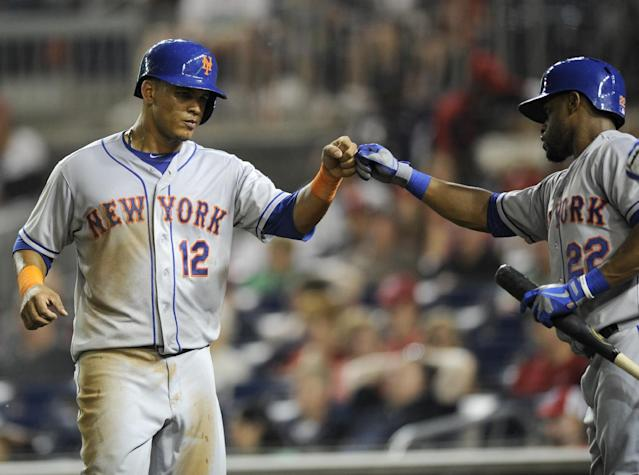 New York Mets' Juan Lagares (12) gets a fist-bump from Eric Young Jr. (22) after scoring from third on a bases-loaded walk to Zack Wheeler during the third inning of a baseball game against the Washington Nationals, Saturday, Aug. 31, 2013, in Washington. (AP Photo/Nick Wass)