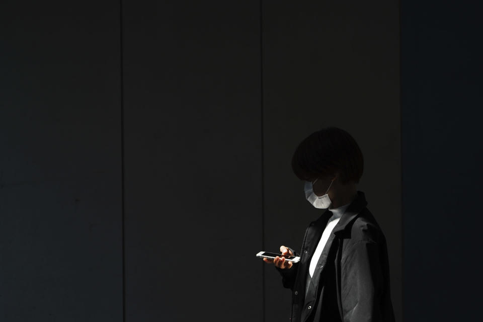 A woman with a protective face mask walks into the shade of an underpass Monday, April 6, 2020, in Tokyo. The new coronavirus causes mild or moderate symptoms for most people, but for some, especially older adults and people with existing health problems, it can cause more severe illness or death. (AP Photo/Eugene Hoshiko)