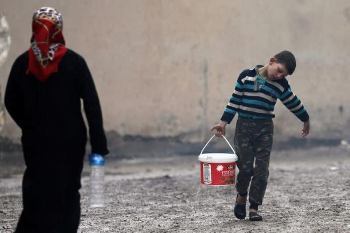 Internally displaced boy carries a bucket filled with water in Azaz