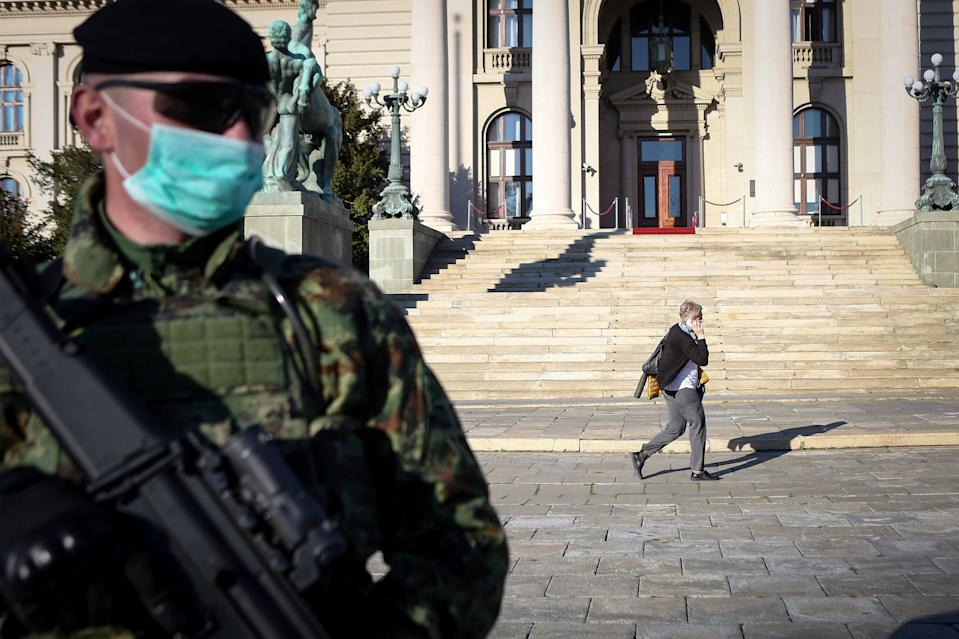 """A Serbian Army soldier wearing gloves and a face masks as preventive measures against COVID-19 (novel Coronavirus) stands guard in front of the National Assembly in Belgrade on March 16, 2020. - Serbia declared a state of emergency on March 15, 2020 to halt the spread of the new coronavirus, shutting down many public spaces, deploying soldiers to guard hospitals and closing the borders to foreigners. Serbia's President Aleksandar Vucic said the new restrictions were necessary to """"save our elderly"""" in the Balkan state of some seven million, which has detected around 55 infections of COVID-19 so far with limited testing. (Photo by Oliver BUNIC / AFP) (Photo by OLIVER BUNIC/AFP via Getty Images)"""