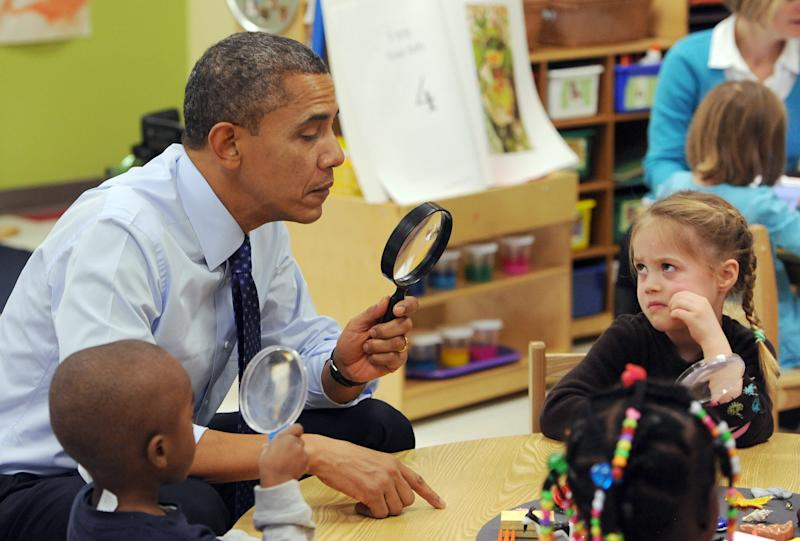President Barack Obama looks through a spy glass as a little girl stares at him during a visit to College Heights Early Childhood Learning Center in Decatur, Ga. on Thursday, Feb. 14, 2013. The president visited the school to highlight their pre-kindergarten program. He is proposing a nationwide initiative for children in pre-kindergarten. (AP Photo/Atlanta Journal-Constitution, Johnny Crawford, Pool)