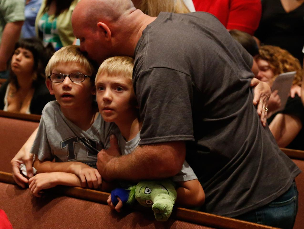 MOORE, OK - MAY 26:  Tornado victims Russell Smith hugs his children and Briarwood Elementary School students, Evan and Justin Smith, during the Oklahoma Strong memorial service held to honor victims of the recent deadly tornado at the First Baptist Church on May 26, 2013 in Moore, Oklahoma. The tornado of EF5 strength and two miles wide touched down May 20 killing at least 24 people and leaving behind extensive damage to homes and businesses. U.S. President Barack Obama visited the area Sunday and promised federal aid to supplement state and local recovery efforts.  (Photo by Sue Ogrocki-Pool/Getty Images)