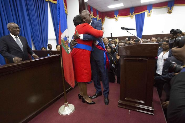 Haiti's President Jovenel Moise hugs his wife Martine after being sworn-in at Parliament in Port-au-Prince, Haiti, Tuesday Feb. 7, 2017. Moise was sworn as president for the next five years after a bruising two-year election cycle, inheriting a struggling economy and a deeply divided society. (AP Photo/Dieu Nalio Chery)