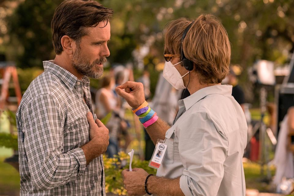 """""""Outer Banks"""" co-creator, executive producer and director Jonas Pate (masked right) talks with actor Charles Esten on the set of the Netflix series' second season."""
