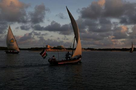 Traditional dhows sail by close to the island of Lamu, Kenya, November 8, 2017. REUTERS/Siegfried Modola
