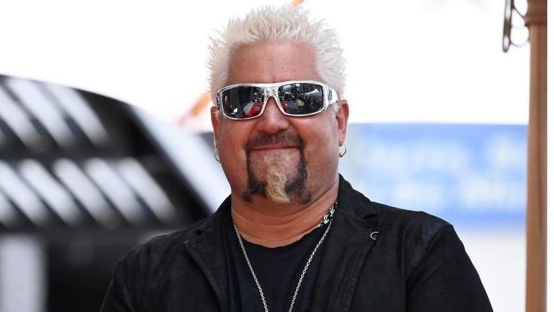 Guy Fieri in sunglasses and a black jacket, smiling
