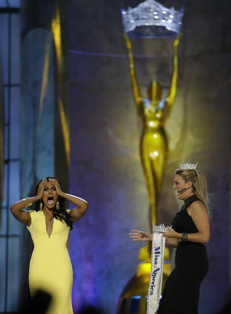 Miss New York Nina Davuluri, left, reacts after winning the Miss America 2014 pageant as Miss America 2013 Mallory Hagan approaches her, Sunday, Sept. 15, 2013, in Atlantic City, N.J. (AP Photo/Julio Cortez)