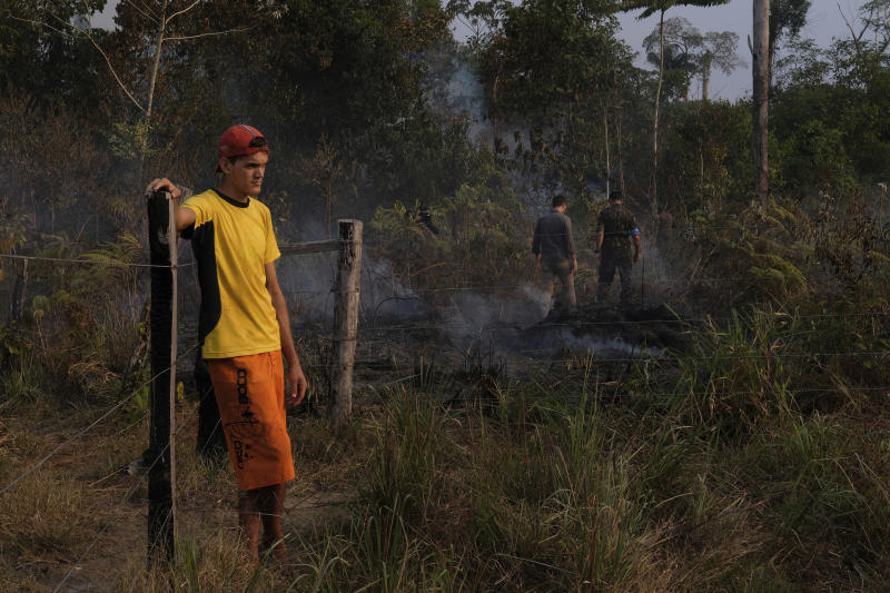 Eric Raauwendaal, left, a livestock farmer stands next to a fence while a fire burns in his family's property, on the border of Jacunda National Forest, in the Amazonian state of Rondonia, Brazil, Thursday, August 29, 2019. Firefighters and members of Brazil's military arrived to Raauwendaal property to help put out a fast-spreading blaze. Raauwendaal said the Amazon must be protected because it's the world's largest rainforest. (AP Photo/Luis Andres Henao)