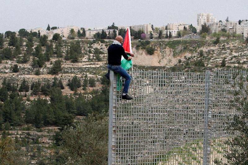A Palestinian man plants his national flag atop an iron fence set up by Israeli security forces between the West Bank village of Beit Jala and the Jerusalem area, on March 30, 2017 during Land Day protest (AFP Photo/Musa AL SHAER)