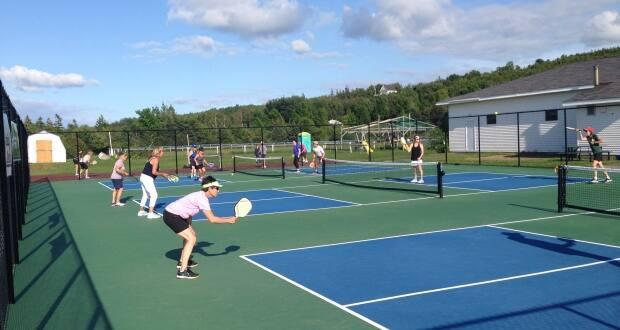 A number of people play pickleball on courts in Arisaig, N.S. (Submitted by Pat Morrison - image credit)