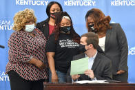 Kentucky Governor Andy Beshear talks with Tamika Palmer, the mother of Breonna Taylor, back row center, following the signing of a partial ban on no-knock warrants at the Center for African American Heritage Louisville, Ky., Friday, April 9, 2021. The bill signing comes after months of demonstrations set off by the fatal shooting of Taylor in her home during a botched police raid. (AP Photo/Timothy D. Easley)