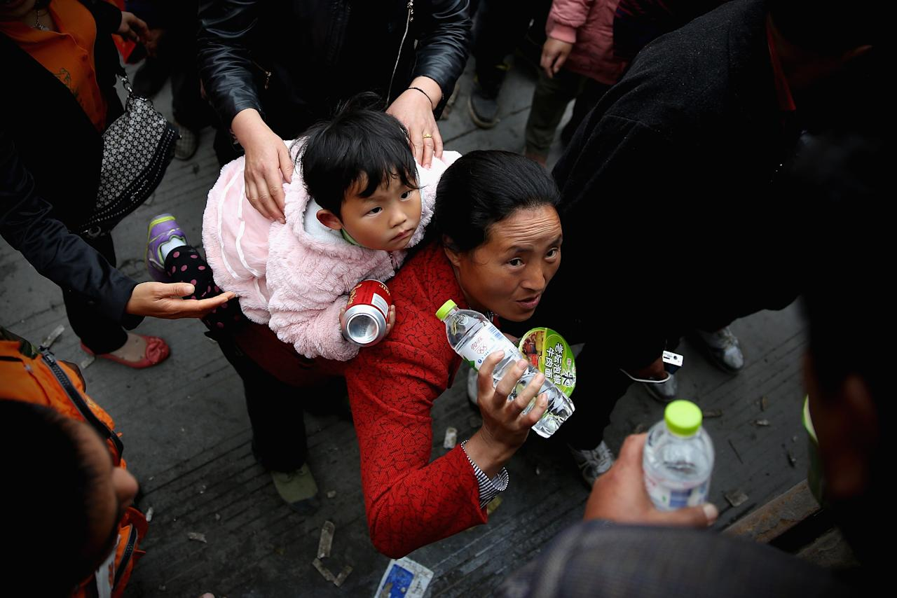 CHENGDU, CHINA - APRIL 22:  Earthquake survivors queue for free food on April 22, 2013 in Lushan of Ya An, China.  A magnitude 7 earthquake hit China's Sichuan province on April 20 claiming over 180 lives and injuring thousands.  (Photo by Feng Li/Getty Images)