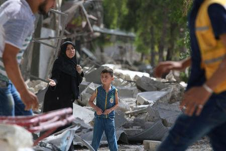 A woman reacts in a damaged site after airstrikes on the rebel held al-Qaterji neighbourhood of Aleppo, Syria. REUTERS/Abdalrhman Ismail