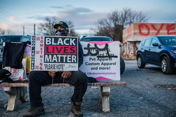 A supporter of Democratic U.S.Senate candidates Jon Ossoff and the Rev. Raphael Warnock sits at a bus-stop with a Black Lives Matter sign on Jan. 4, 2021 in Atlanta.