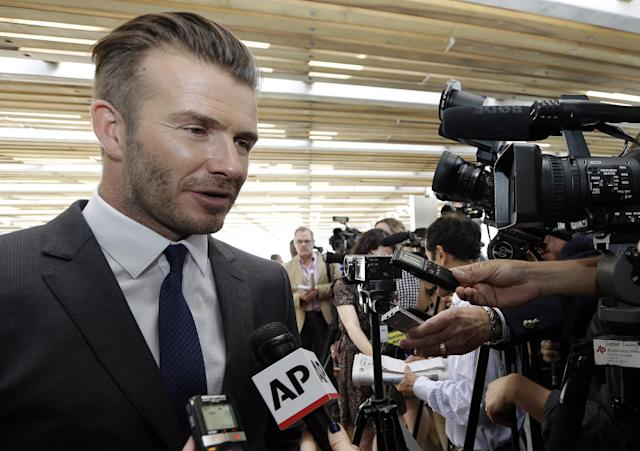 Former England soccer star David Beckham responds to a question following a news conference where he announced he will exercise his option to purchase a Major League Soccer expansion team in Miami, Wednesday, Feb. 5, 2014, in Miami. (AP Photo/Lynne Sladky)