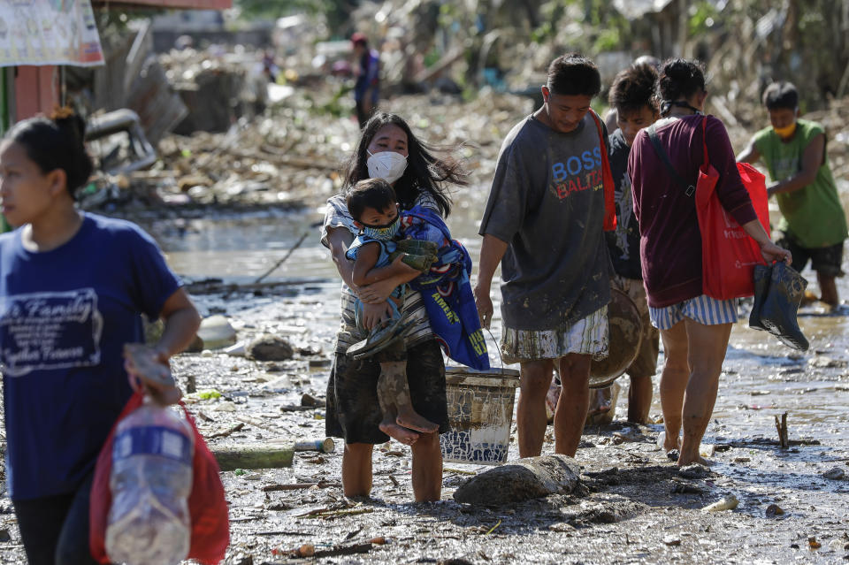 A woman carries her daughter through debris and floods in the typhoon-damaged Kasiglahan village in Rodriguez, Rizal province, Philippines on Friday, Nov. 13, 2020. Thick mud and debris coated many villages around the Philippine capital Friday after Typhoon Vamco caused extensive flooding that sent residents fleeing to their roofs and killing dozens of people. (AP Photo/Aaron Favila)