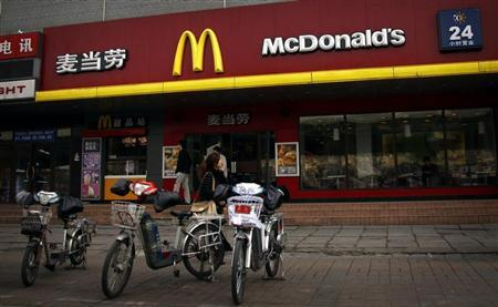 A woman walks past electric bikes sitting outside a McDonalds fast-food outlet in central Beijing