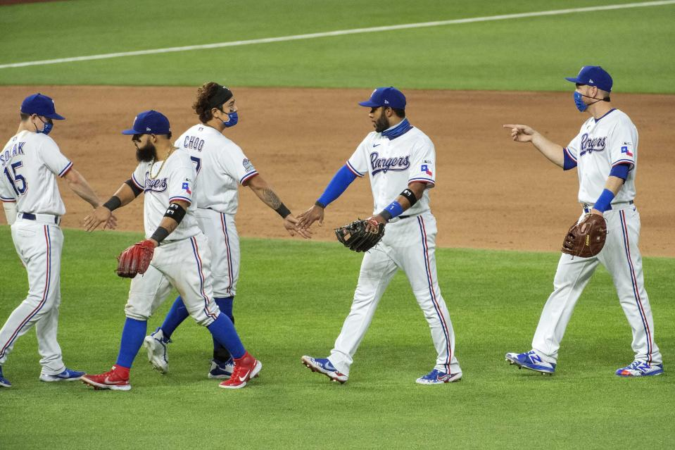 From left to right, Texas Rangers Nick Solak, Rougned Odor, Shin-Soo Choo, Elvis Andrus and Todd Frazier congratulate each other after they defeated the Colorado Rockies in an opening day baseball game Friday, July 24, 2020, in Arlington, Texas. (AP Photo/Jeffrey McWhorter)