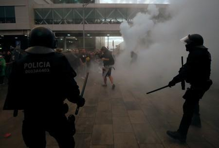 Police officers and protesters stand amid smoke during a demonstration at the airport, after a verdict in a trial over a banned independence referendum, in Barcelona