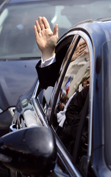 France's President and conservative candidate for re-election in 2012, Nicolas Sarkozy, from his car to supporters as he leaves a campaign meeting in Sables d'Ollonne, western France, Friday, May 4, 2012. The final polls before France's presidential election Sunday show a shrinking gap between President Nicolas Sarkozy and Socialist challenger Francois Hollande, but still predict a Hollande victory. (AP Photo/Eric Feferberg, Pool)