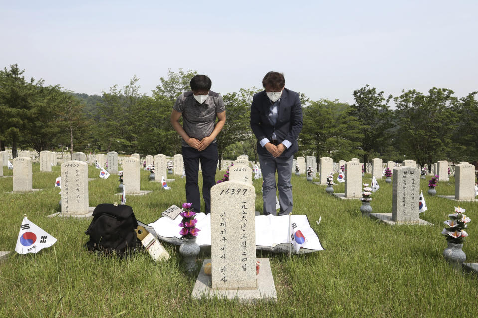 South Korean Park Tae-soon, left, and Park Young-soon wearing face masks to help protect against the spread of the new coronavirus pay their respects in front of the gravestone of their father Park Gong-jin who died during the Korean War, on Memorial Day at the national cemetery in Seoul, South Korea, Saturday, June 6, 2020. (AP Photo/Ahn Young-joon)