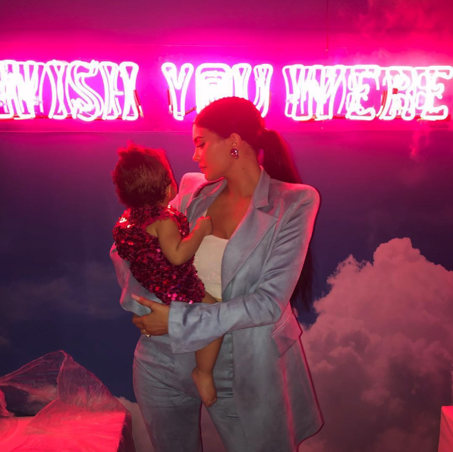 """Kylie Jenner posted a photo in front of a neon sign at daughter Stormi Webster's first birthday party, writing she """"had to go all out for my baby."""" (Credit: Kylie Jenner via Instagram)"""