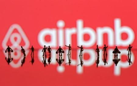 A 3D printed people's models are seen in front of a displayed Airbnb logo in this illustration