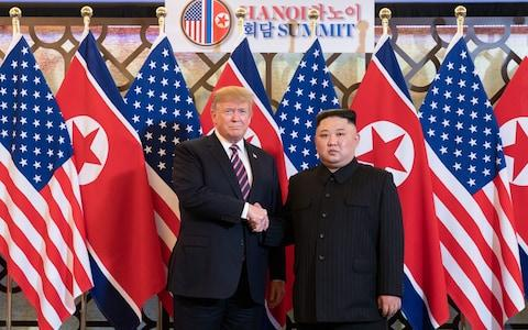 Donald Trump and Kim Jong-un shake hands in front of the US and North Korean flags at the Hanoi Summit earlier this year - Credit: White House Photo/Shealah Craighead/Handout