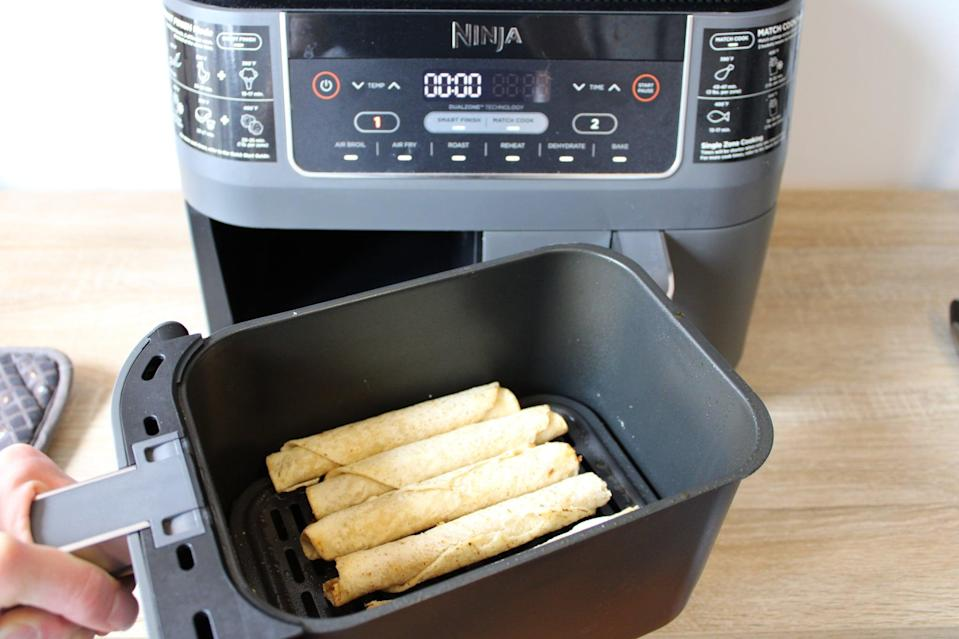 <p>After four minutes, pause the cooking process to shake the basket. You can also turn the taquitos by hand, but I find their shape is quite conducive to a good shake! Then, return the taquitos to the air fryer for four more minutes.</p>