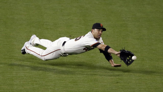 San Francisco Giants' Travis Ishikawa can't catch a double hit by Kansas City Royals' Omar Infante during the fifth inning of Game 5 of baseball's World Series Sunday, Oct. 26, 2014, in San Francisco. (AP Photo/Eric Risberg)