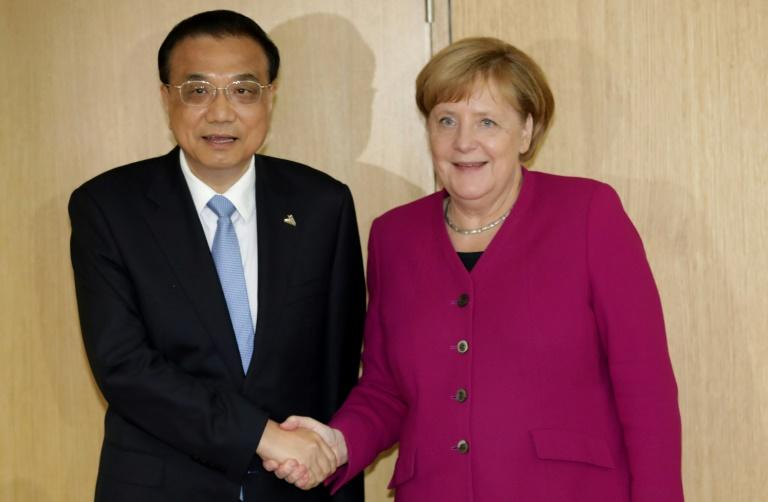 German Chancellor Angela Merkel (R) shakes hands with China's Prime Minister Li Keqiang ahead of a meeting on the sidelines of an EU-ASEM leaders meeting at the European Council in Brussels on October 19, 2018