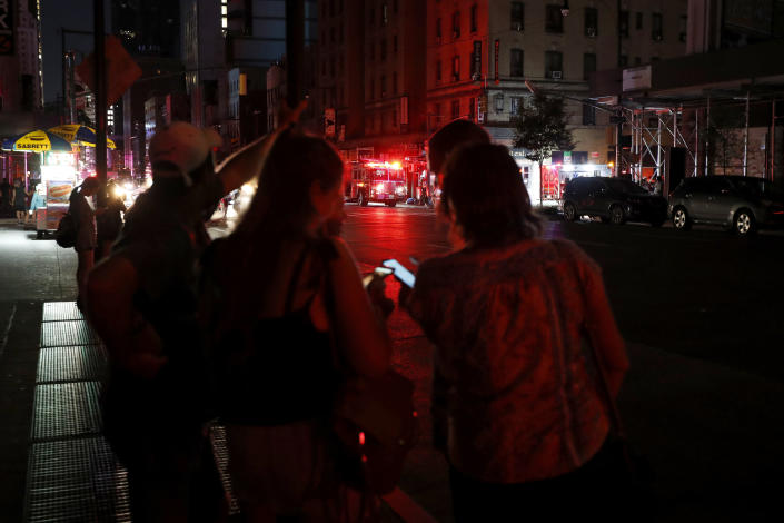 Pedestrians looks at their cellphones during a power outage in midtown Manhattan, Saturday, July 13, 2019, in New York. (Photo: Michael Owens/AP)