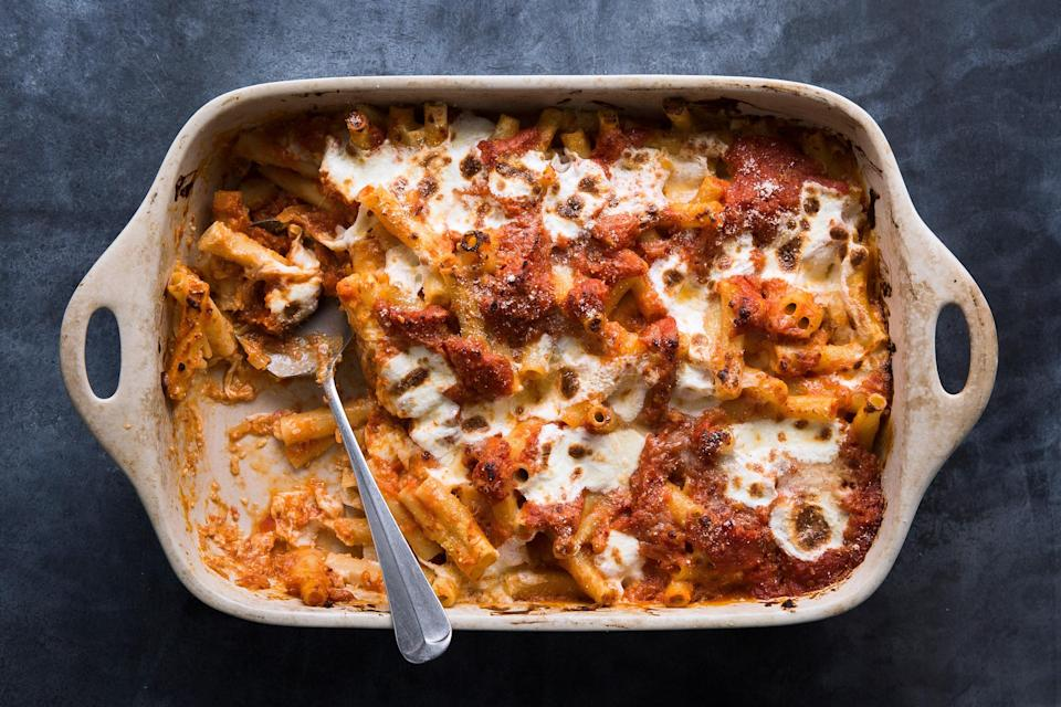 "We know ricotta is a traditional addition to baked ziti, but it has a tendency to get dry and grainy when baked. Our update uses a creamy Parmesan béchamel, in addition to a tangy tomato sauce, which together make for a super flavorful finished dish—that won't dry out in the oven. <a href=""https://www.bonappetit.com/recipe/bas-best-baked-ziti?mbid=synd_yahoo_rss"" rel=""nofollow noopener"" target=""_blank"" data-ylk=""slk:See recipe."" class=""link rapid-noclick-resp"">See recipe.</a>"