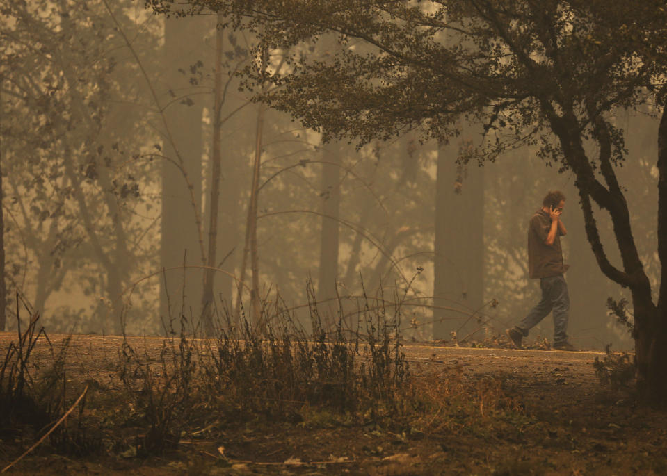 Pictured is a man walking through burnt land.