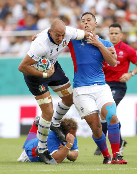 Italy's Sergio Parisse, left, carries the ball while being tackled by Namibia during the Rugby World Cup Pool B game between Italy and Namibia in Osaka, western Japan, Sunday, Sept. 22, 2019. (Ichiro Sakano/Kyodo News via AP)