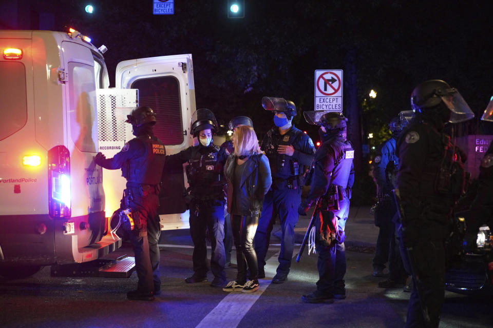 A female protester is loaded into a van after being arrested while rallying at the Mark O. Hatfield United States Courthouse on Saturday, Sept. 26, 2020, in Portland, Ore. The rally came as Portland has seen nearly nightly protests since the police killing of George Floyd in late May. (AP Photo/Allison Dinner)