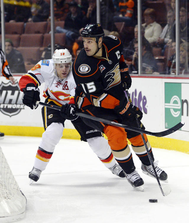 Anaheim Ducks center Ryan Getzlaf, right, moves the puck as Calgary Flames center Matt Stajan defends during the first period of an NHL hockey game, Friday, Nov. 29, 2013, in Anaheim, Calif. (AP Photo/Mark J. Terrill)