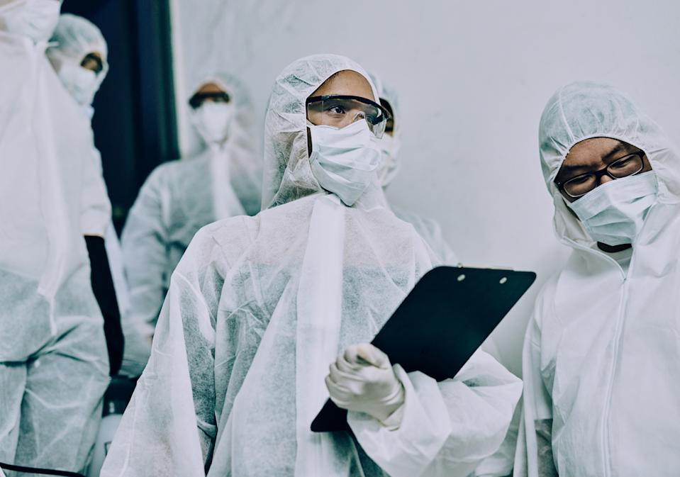 Shot of a group of healthcare workers wearing hazmat suits working together to control an outbreak