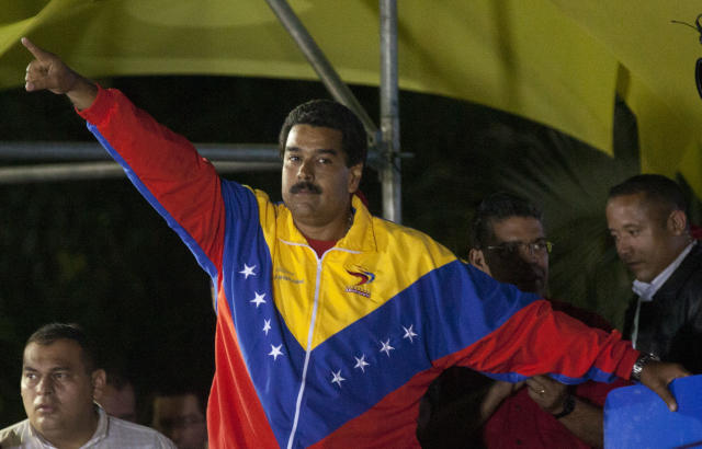 Venezuela's newly elected President Nicolas Maduro celebrates his victory after the official results of the presidential elections were announced, at the Miraflores Palace in Caracas, Venezuela, late Sunday, April 14, 2013. Maduro, Hugo Chavez's hand-picked successor, won a razor-thin victory in Sunday's special presidential election, edging the opposition leader Henrique Capriles by only about 300,000 votes, electoral officials announced. (AP Photo/Ramon Espinosa)