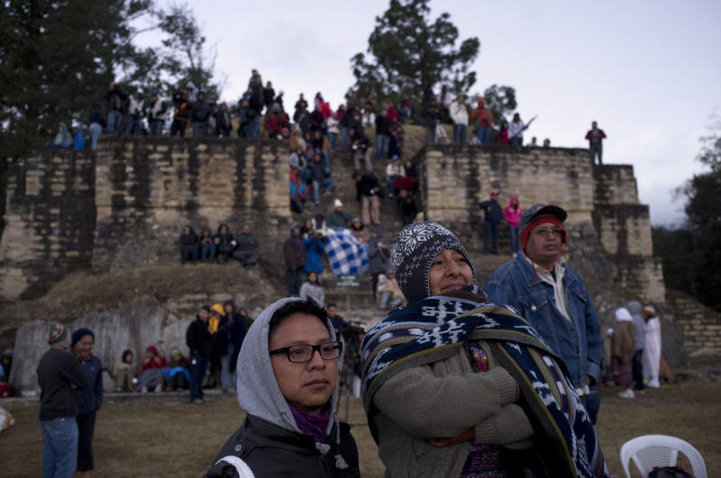 People watch in a ceremony at the Iximche archeological site to mark the end of the 13th Oxlajuj B'aktun in Tecpan, Guatemala, as the sun rises on Friday, Dec. 21, 2012. The end of the 13th Oxlajuj B'aktun marks a new period in the Mayan calendar, an event only comparable in recent times with the new millennium in 2000. While the Mayan calendar cycle has prompted a wave of doomsday speculation across the globe, few in the Mayan heartland believe the world will end on Friday. (AP Photo/Moises Castillo)