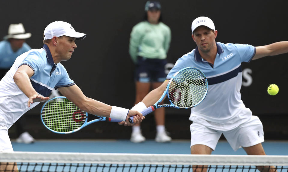 Bob, left, and Mike Bryan of the U.S. during their first round doubles match against India's Rohan Bopanna and Japan's Yasutaka Uchiyama at the Australian Open tennis championship in Melbourne, Australia, Wednesday, Jan. 22, 2020. (AP Photo/Dita Alangkara)