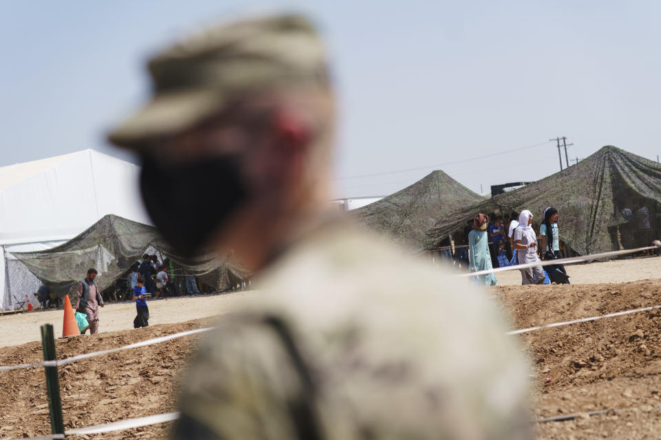 A soldier stands outside a dining hall at Fort Bliss' Doña Ana Village, in New Mexico, where Afghan refugees are being housed, Friday, Sept. 10, 2021. The Biden administration provided the first public look inside the U.S. military base where Afghans airlifted out of Afghanistan are screened, amid questions about how the government is caring for the refugees and vetting them. (AP Photo/David Goldman)