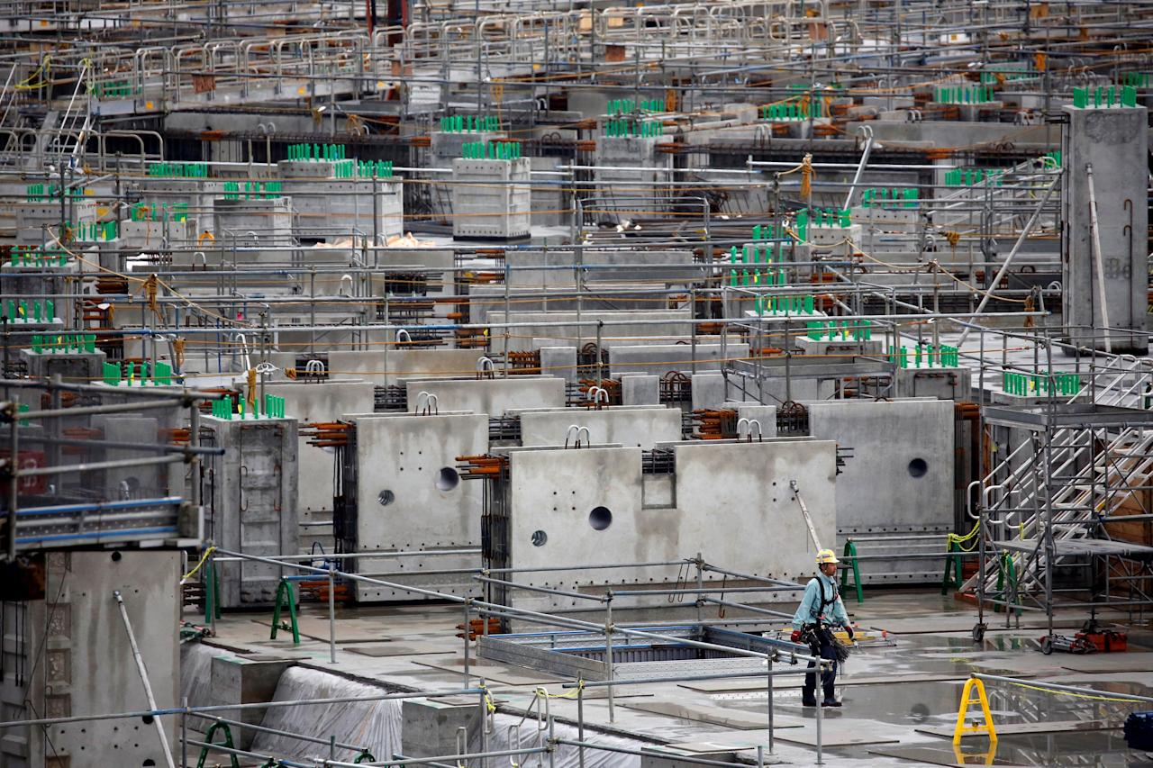 FILE PHOTO : A worker walks at a construction site of New National Stadium for the Tokyo 2020 Olympics and Paralympics in Tokyo, Japan May 26, 2017. REUTERS/Issei Kato/File Photo