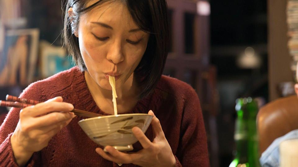Mid woman eating noodle.