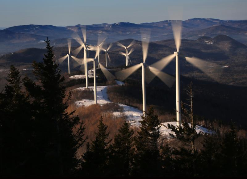 FILE - In this March 19, 2019 file photo, the blades of wind turbines catch the breeze at the Saddleback Ridge wind farm in Carthage, Maine. Scientists say emissions worldwide need to start falling sharply from next year if there is to be any hope of achieving the Paris climate accord's goal of capping global warming at 1.5 degrees Celsius (2.7 Fahrenheit). (AP Photo/Robert F. Bukaty, File)