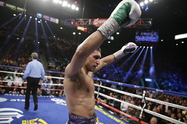 England's Amir Khan, center, raises his arms in victory at the end of his silver welterweight title boxing fight against Luis Collazo Saturday, May 3, 2014, in Las Vegas. Referee Vic Drakulich is at left. (AP Photo/Isaac Brekken)