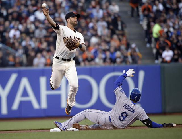 San Francisco Giants second baseman Brandon Hicks, top, turns a double play over Los Angeles Dodgers' Dee Gordon (9) on a ground ball by Hanley Ramirez during the first inning of a baseball game on Wednesday, April 16, 2014, in San Francisco. (AP Photo/Marcio Jose Sanchez)