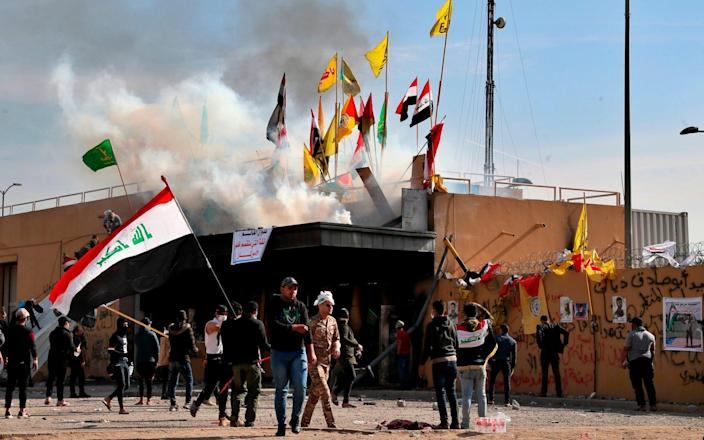 Pro-Iranian militiamen and their supporters set a fire while US soldiers fired tear gas during a sit-in in front of the US embassy in Baghdad - AP