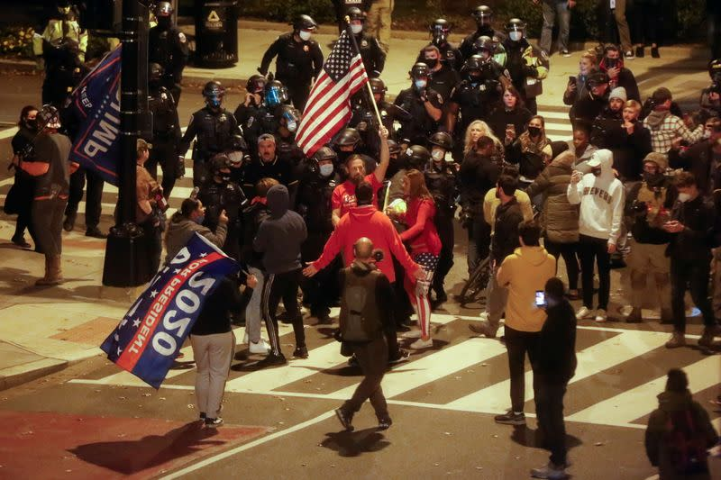 Law enforcement personnel keep an eye as supporters of U.S. President Donald Trump and supporters of U.S. President-elect Joe Biden exchange words on a street, in Washington
